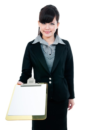 Portrait of a cute young Asian businesswoman presenting clipboard with copy space over white background. photo