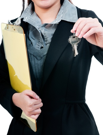 Close-up of a businesswoman holding clipboard and keys. photo