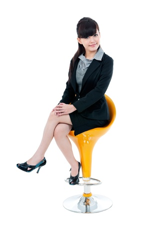 Portrait of a cute young Asian businesswoman sitting on a stool , isolated on white background. photo