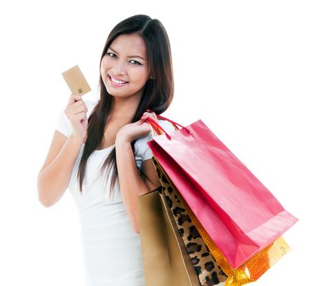 tarjeta de credito: Retrato de una joven mujer que sostiene la tarjeta de cr�dito y de compras lindo bolsas contra el fondo blanco