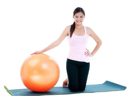 donna in ginocchio: Donna di forma fisica in ginocchio con la sfera dell'equilibrio