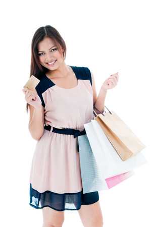 Portrait of a beautiful young woman holding shopping bags and credit card over white background photo