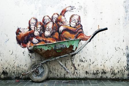 ernest: Kuching, Malaysia - April 27: Wall mural of orangutans in wheelbarrow painted by Lithuanian street artist Ernest Zacharevic along Jalan Power, Kuching, Sarawak on April 27, 2014.