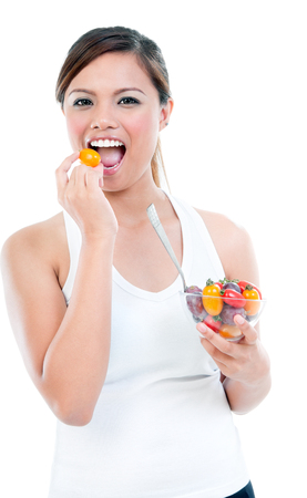 Portrait of a healthy fitness woman eating a bowl of fruits, isolated on white. Stok Fotoğraf