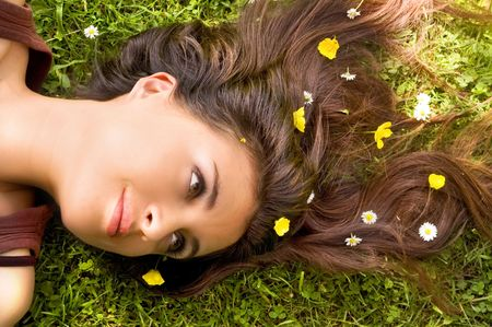 Attractive Woman with Flowers in her hair lying down.  Stock Photo