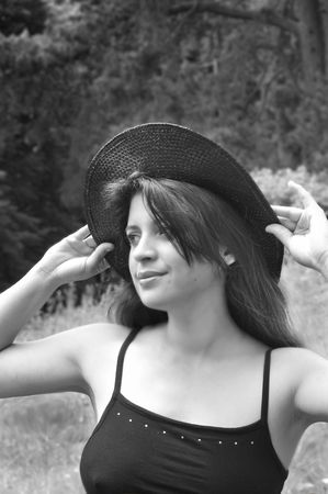 a black and white of a happy, attractive young lady wearing a hat in summer