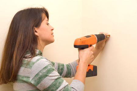 Woman using a cordless screwdriver.