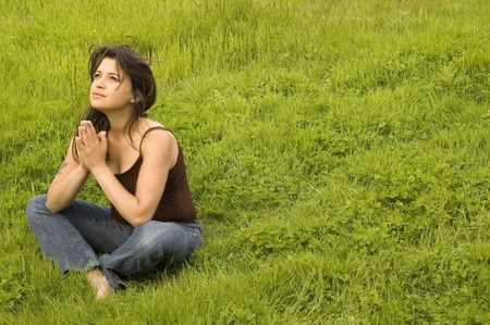 Young woman sitting in praying pose (more images in portfolio) Stock Photo
