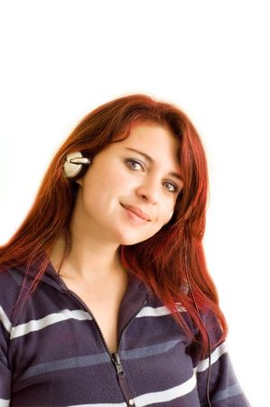 Pretty redhead wearing set of headphones.