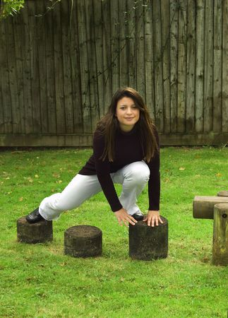 Woman climbing over stepping stones in the playground.   Stock Photo