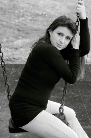 black and white image of pretty young female on a swing