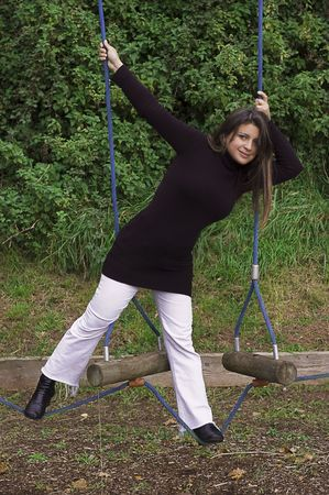 YOung woman playing on obstacle course in the playpark.