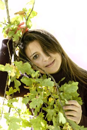 Woman lovingly holding leaves on a tree.