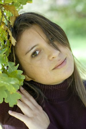 Pretty young woman against green leaves Stock Photo