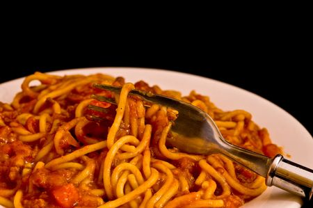 a plate of spaghetti bolognese with a fork