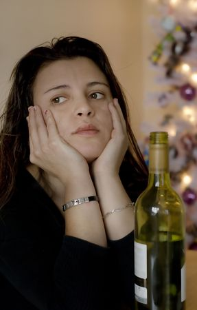 Depressed woman at christmas time and a bottle of wine. Stock Photo - 3965970