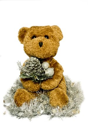 a brown bear hold a christmas decoration sat in tinsel