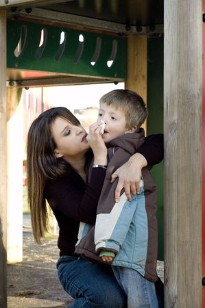 Mum caringly wipes her son's nose in a playground