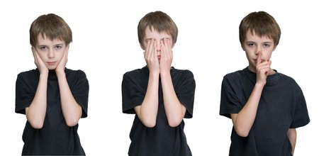 a young male child depicting the three wise monkies old saying hear, see and speak no evil.  photo