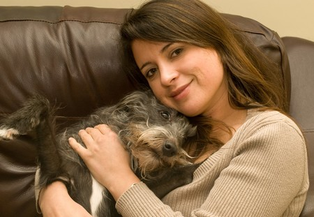 a pretty young woman cuddling her cute scruffy dog  Stock Photo