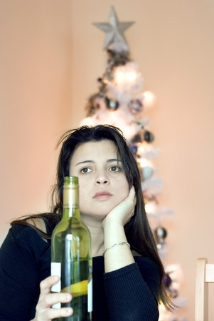 a depressed woman drinking a bottle of wine. Stock Photo