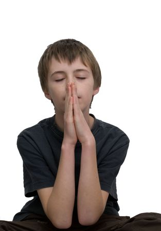 an isolated image of a you boy / teen praying with his eye closed. Standard-Bild