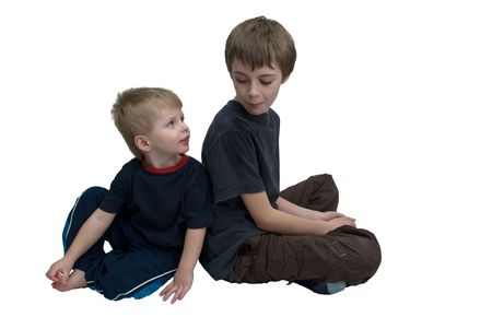 Two brothers sitting back to back looking towards each other, isolated.