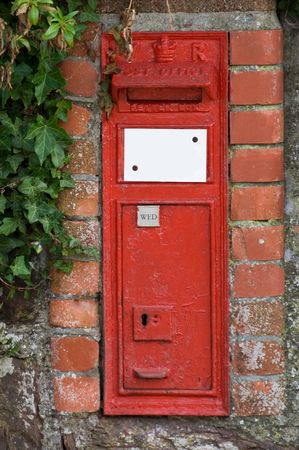 an overgrown old bristish post box embedded in a brick wall.