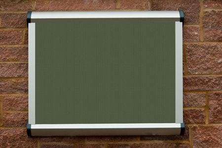 a blank green texture public notice board, hanging on a red stone wall. Standard-Bild
