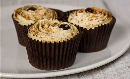 a close up of three delicious chocolate and cherry cup cakes sat upon a white plate.