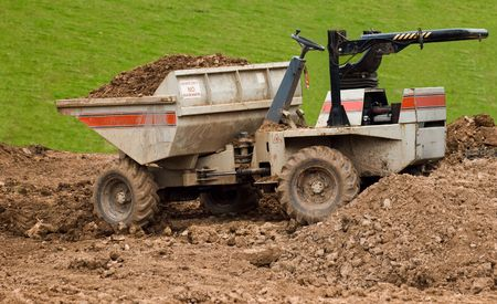 illegally: a dumper truck illegally left with its bucket full, keys in the ignition and its roll bar folded down on a building site easily accessible to the public. Stock Photo