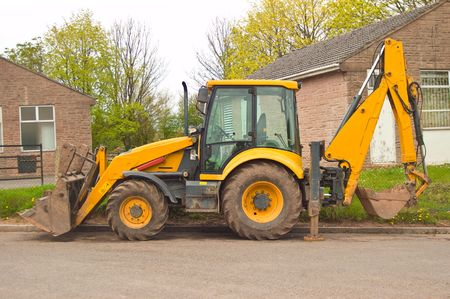 a parked earth mover with stabalising legs down and bucket slightly raised