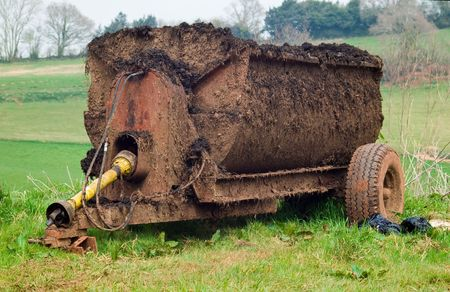 muck: an old well used muck spreader parked on a grass bank with fields in the background.