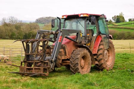 a new tractor with attached grapple-rake in a field of lush green fresh grass parked in front of a sheep and lamb enclosure.