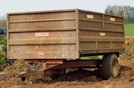 A rusty well used scruffy farm trailer parked on some manure and mud, with fields and tress in the background. Standard-Bild