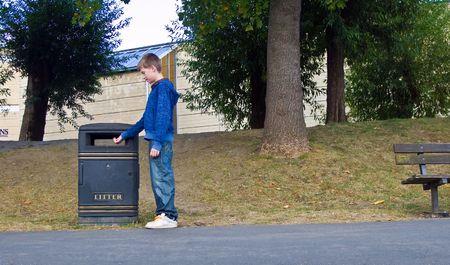 ni�os reciclando: una imagen de un adolescente responsable poniendo la basura en la papelera en lugar de lanzarlo en el piso.