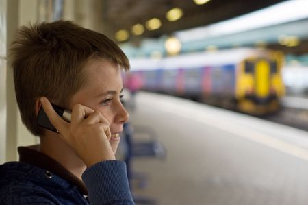 a teenage boy laughing and talking on a mobile phone at a train station.