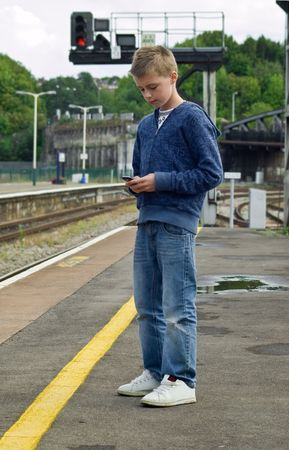 a young teenager using his mobile phone to send a mms or sms message while waiting on a train station platform