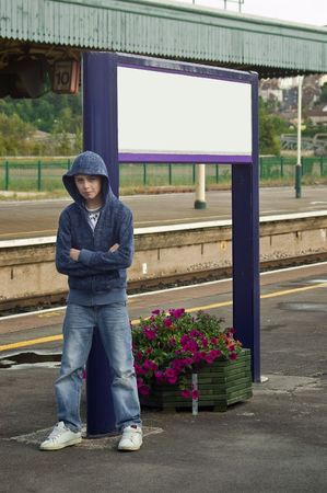 a Hoody or Thug leaning againts a sign post at a train station looking menacing  photo