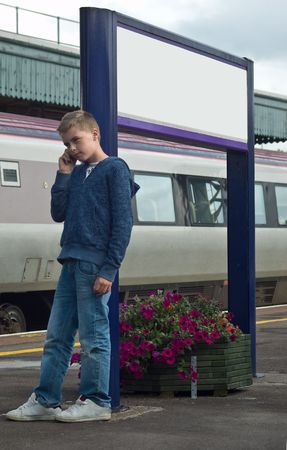 an image of a young teenage boy talkuing on a mobile phone at a train station, leaning against a sign post.