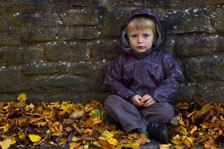 a lonely looking young child sat against a wall with autumn leafs all around him. Stock Photo