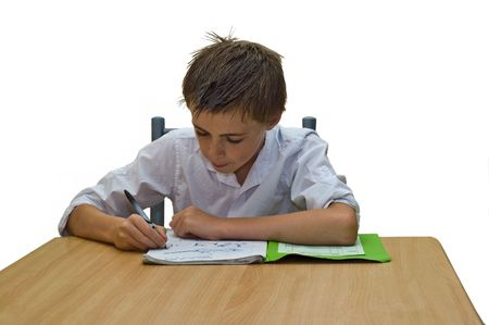 an isolated image of a teenage boy doing his school work  homework sat at a table.