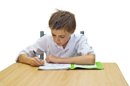 an isolated image of a teenage boy doing his school work / homework sat at a table.