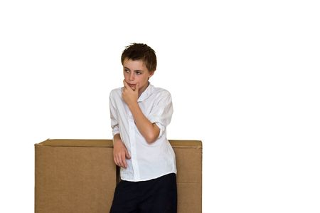 an image of a disheveled young teen stood thinking outside a large cardboard box, depicting the common phrase  Stock Photo