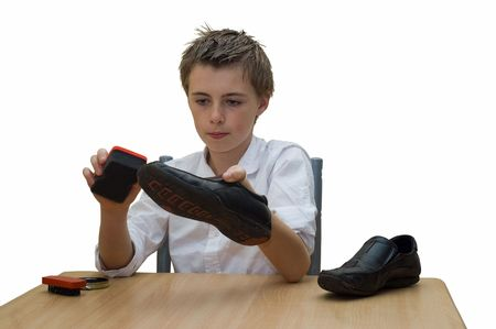 the sole of the shoe: a young teenage boy sat at the table polishing his school shoes using a brush and buffing sponge. Stock Photo