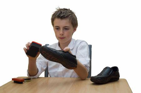 zapatos escolares: un joven adolescente se sent� en la mesa de pulir sus zapatos de escuela, utilizando un pincel y esponja de buffing. Foto de archivo
