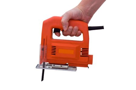 an isolated over white image of a caucasian mans hand holding an orange electric jigsaw.  (please do not mistake the texture of the tool for noise)