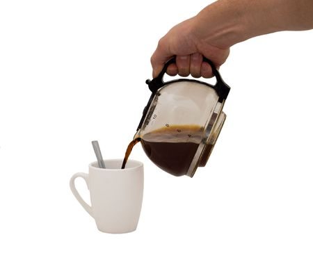 an isolated over white image of a caucasian mans hand holding and pouring coffee into a white mug complete with spoon.