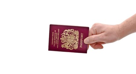 an isolated over white caucasian mans hand holding a European Union British passport