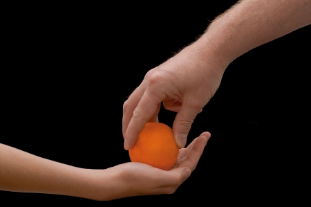 an isolated over black image of a caucasian man giving a caucasian child an lush juicy looking Orange.